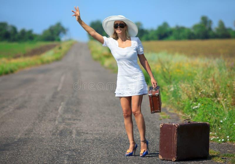 De vrouw met koffer houdt de auto tegen stock foto's