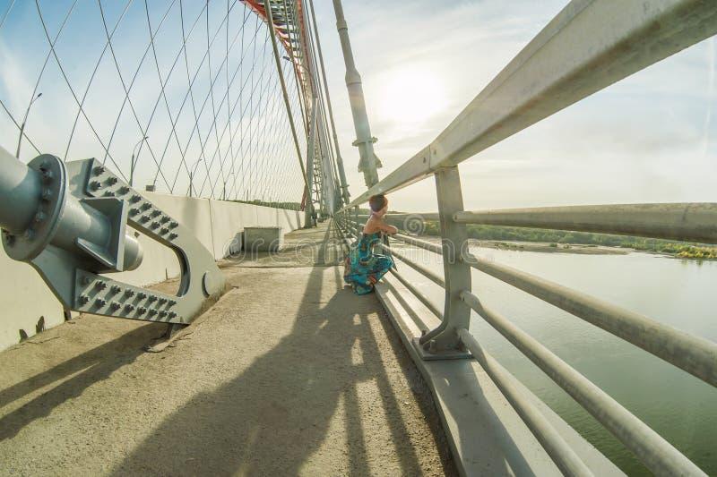 De vrouw met kort kapsel, gekleed in blauwe kleding, wandelt langs de brug die, die de stad bekijken en op zonnige mening, over w stock foto's