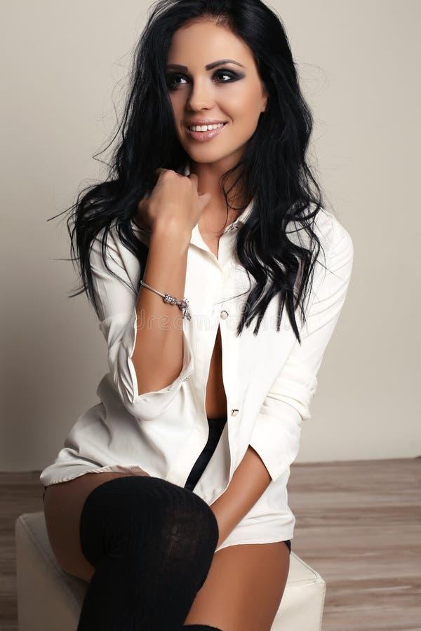 De vrouw met lang donker haar en heldere make-up, draagt elegant wit overhemd stock afbeeldingen