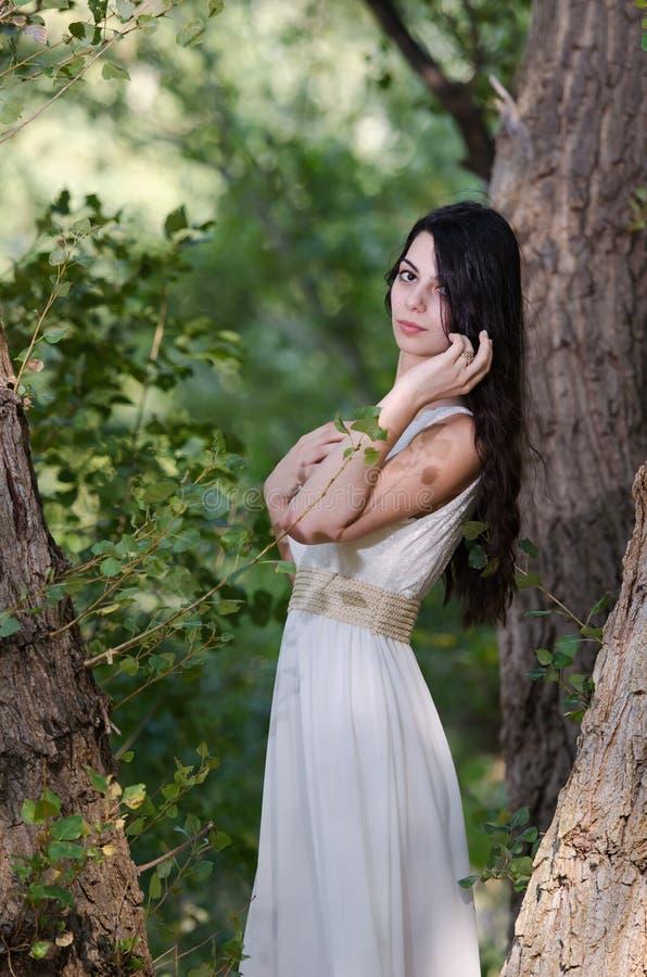 De vrouw met lang haar die witte kleding dragen, stelt in het bos stock foto