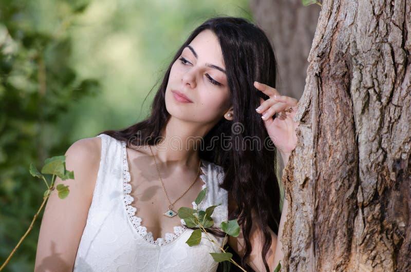 De vrouw met lang haar die witte kleding dragen, stelt in het bos royalty-vrije stock afbeelding
