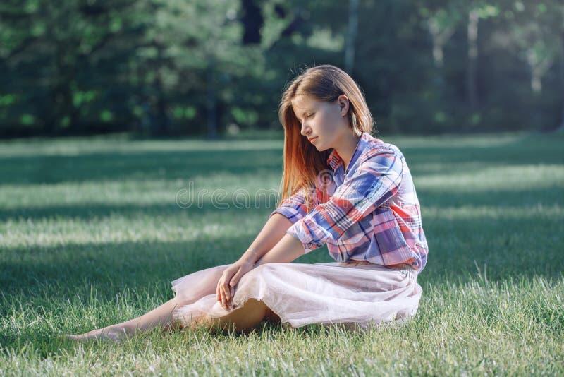 De vrouw met lang rood haar in plaidoverhemd en de roze tutu Tulle begrenzen, zittend op gras stock afbeeldingen