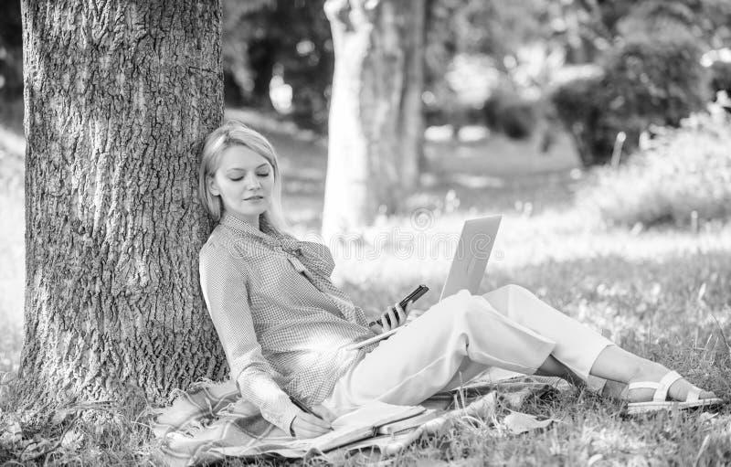 De vrouw met laptop het computerwerk leunt in openlucht op boomboomstam Het meisjeswerk met laptop in park zit op gras naughty stock afbeelding