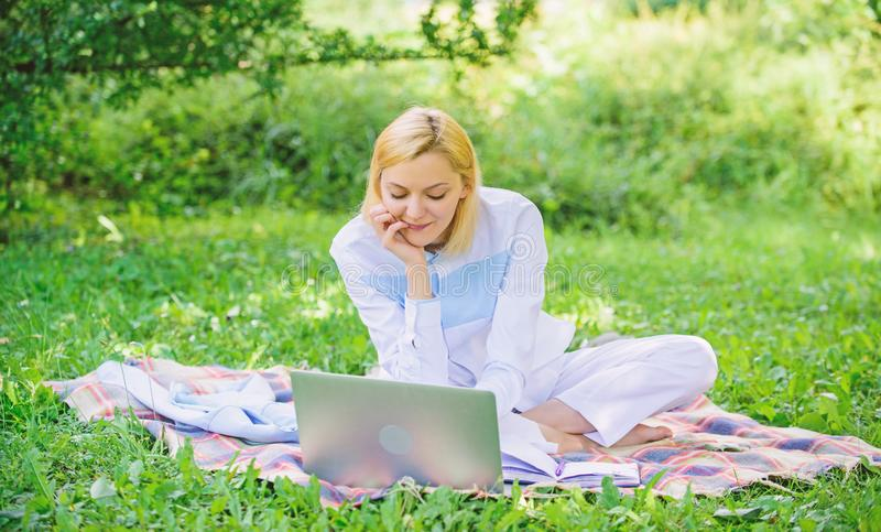De vrouw met laptop of het notitieboekje zit op weide van het deken de groene gras Het bedrijfsdame freelancer werk in openlucht  royalty-vrije stock foto's