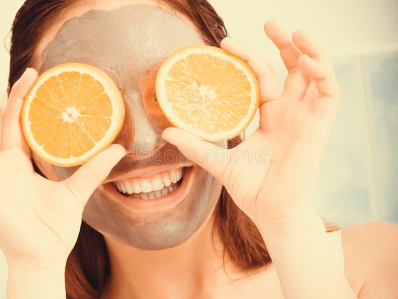 De vrouw met modder gezichtsmasker houdt oranje plak stock afbeelding