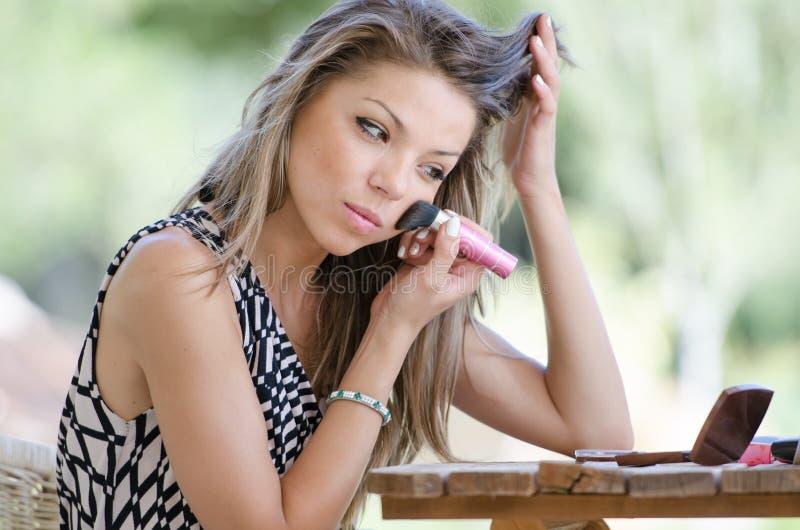 De vrouw met mooi gezicht doet buiten haar make-up royalty-vrije stock foto