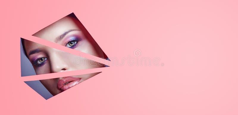 De vrouw met mooie heldere make-up en roze lippenstift kijkt door driehoekige spleten in roze document Adverterende schoonheidsmi royalty-vrije stock foto