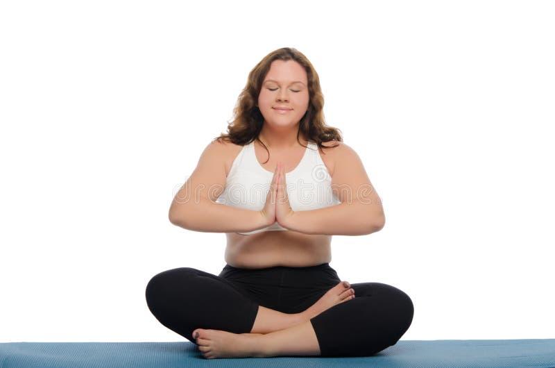 De vrouw met overgewicht mediteert op mat stock afbeelding