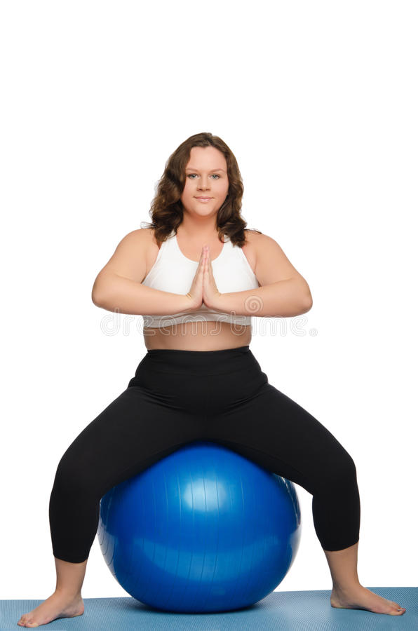 De vrouw met overgewicht zit op blauwe bal stock afbeelding
