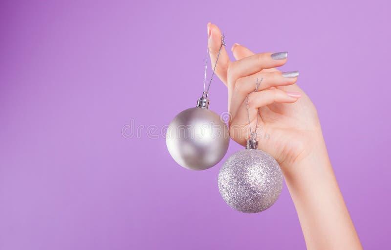 De vrouw met roze en zilveren manicure houdt zilveren Kerstmisballen stock afbeeldingen