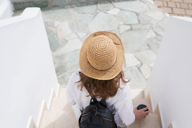 De vrouw met rugzak in een strohoed en document kop van koffie zit op de stappen en ontspant van de toevluchtstad Individuele rei stock foto's