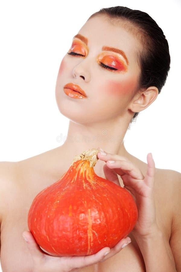 De vrouw met sinaasappel maakt omhoog het houden van pompoen stock foto's