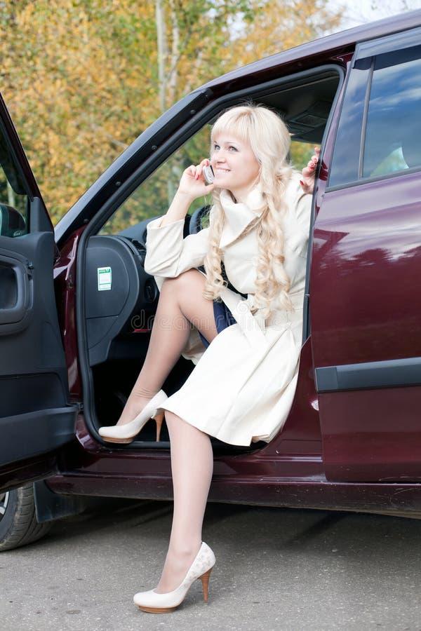 De vrouw met telefoon in de auto stock foto's