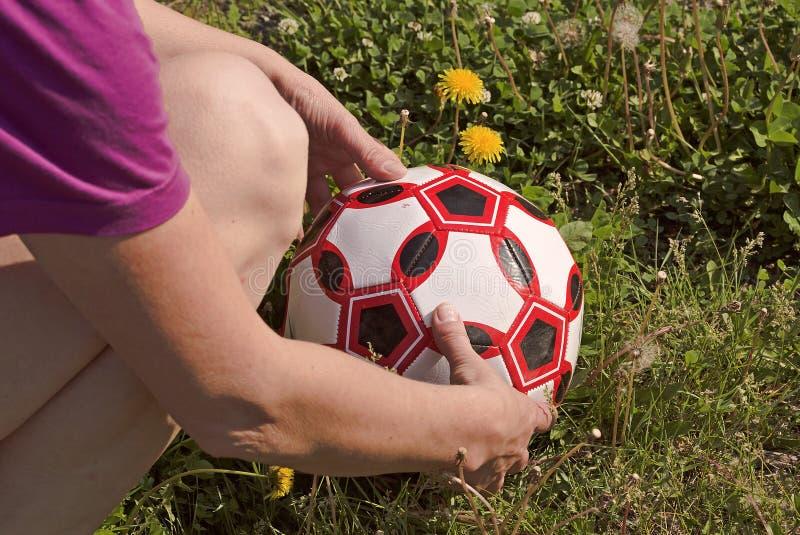 De vrouw met twee handen veegt de voetbalbal op het gras af royalty-vrije stock foto's