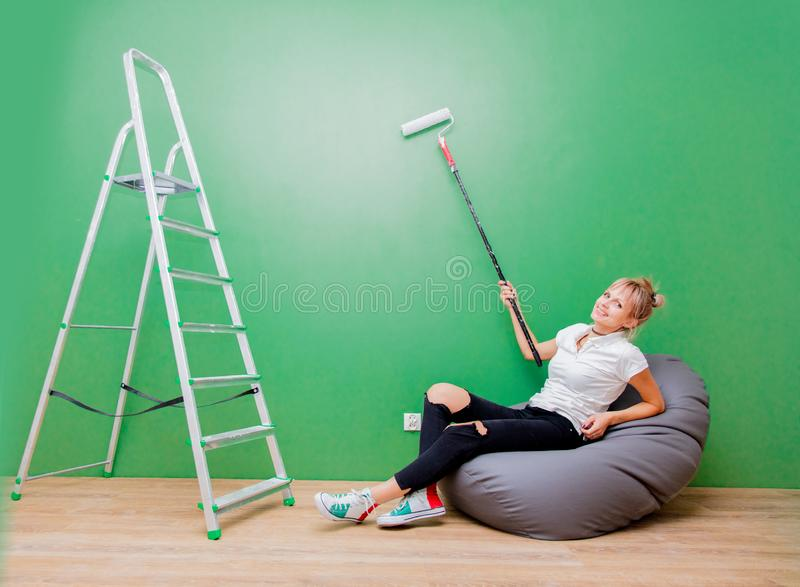 De vrouw met verfrol heeft een rust in eigen huis stock afbeelding