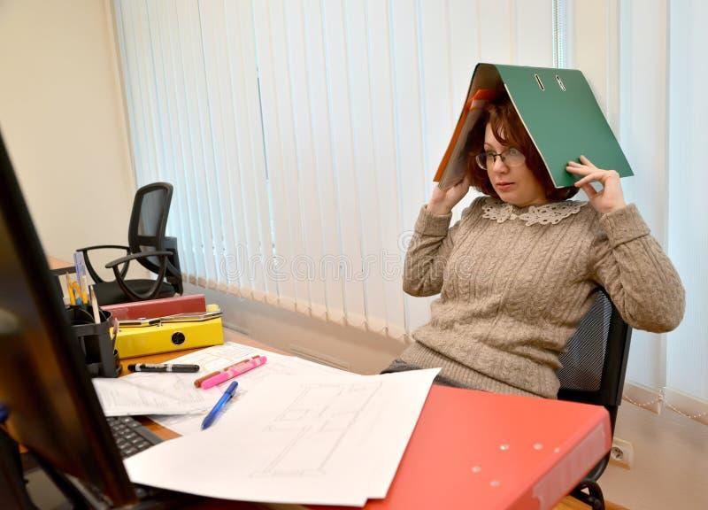 De vrouw met verschrikking kijkt in de monitor, die de omslag met documenten op het hoofd houden stock fotografie
