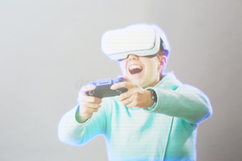 De vrouw met virtuele werkelijkheidshoofdtelefoon speelt spel Beeld met hologrameffect stock afbeelding
