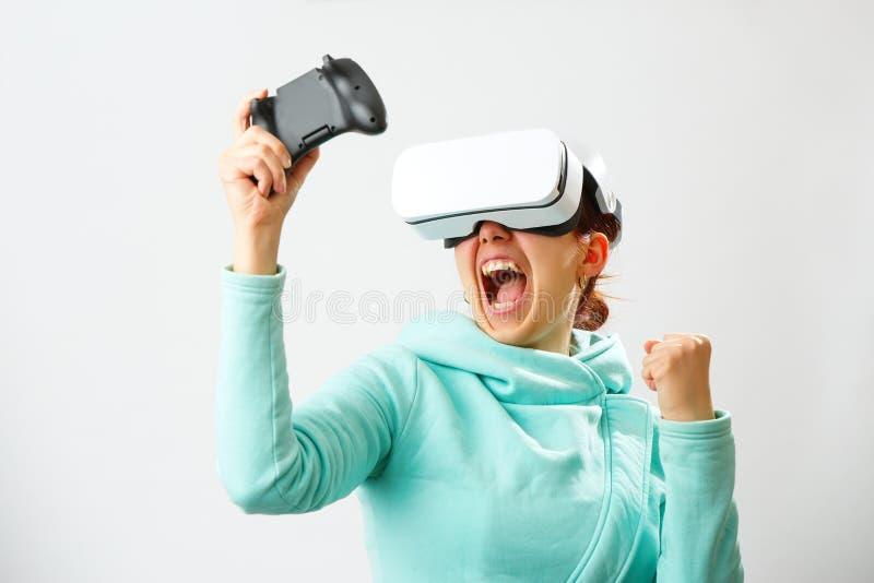 De vrouw met virtuele werkelijkheidshoofdtelefoon speelt spel stock afbeelding