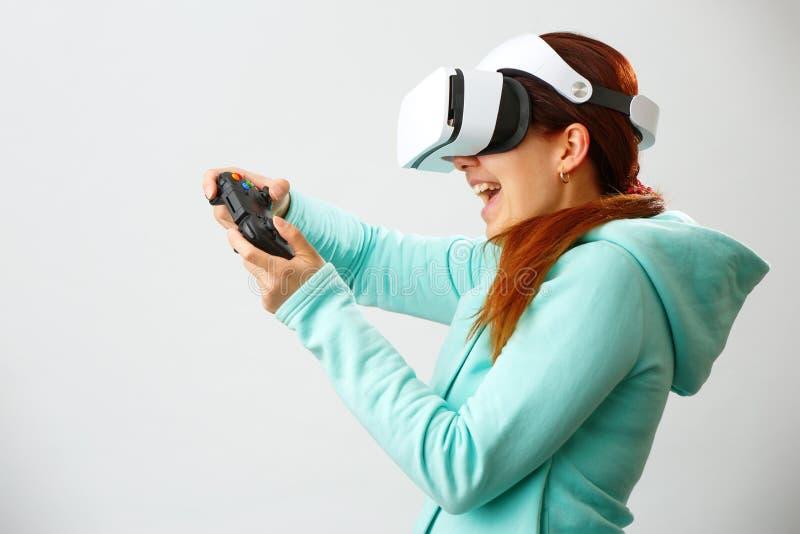 De vrouw met virtuele werkelijkheidshoofdtelefoon speelt spel royalty-vrije stock afbeeldingen