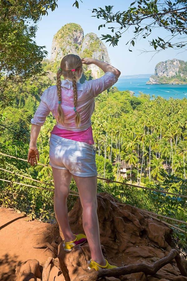 De vrouw met vlechten in roze overhemd bevindt zich op de bovenkant van de heuvel en let op over de wildernissen en twee zandige  stock afbeelding