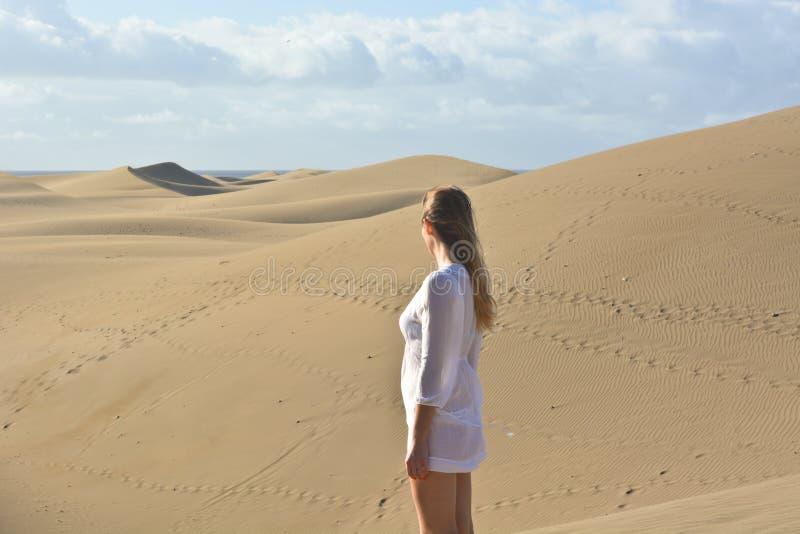 De vrouw met witte kleding in de woestijn stock foto's