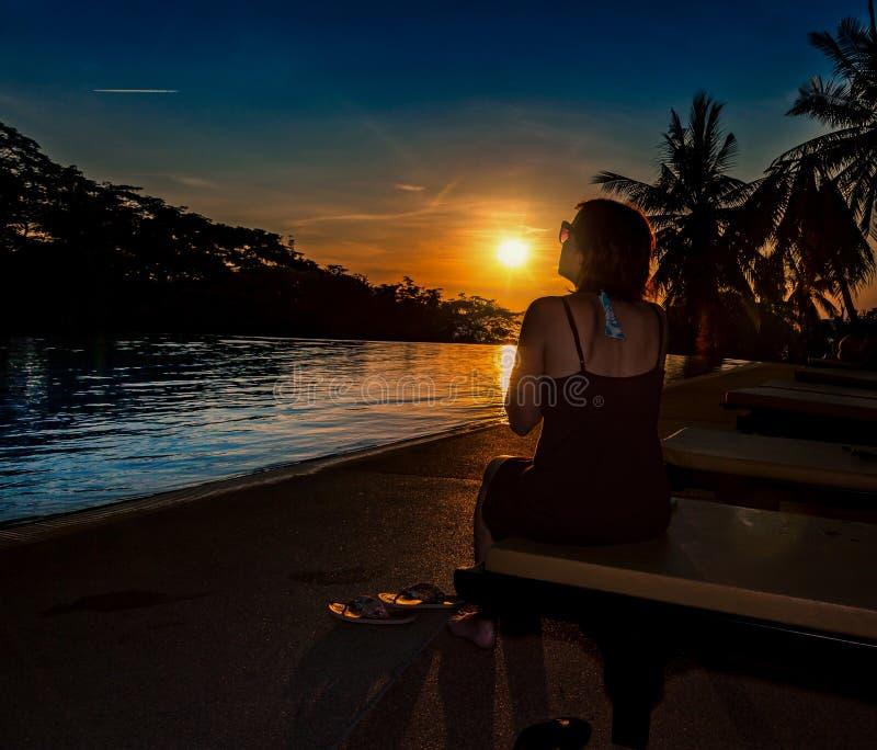 De vrouw met zonnebril onderzoekt de zonsondergang stock foto's