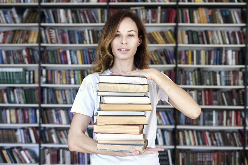 De vrouw de modelstudent met boeken bij bibliotheek bos van boeken houdt, kijkt slim, glimlachend aan camera boekenrekken bij de  stock afbeelding