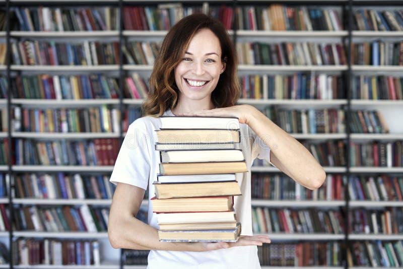 De vrouw de modelstudent met boeken bij bibliotheek bos van boeken houdt, kijkt slim, glimlachend aan camera boekenrekken bij de  stock afbeeldingen