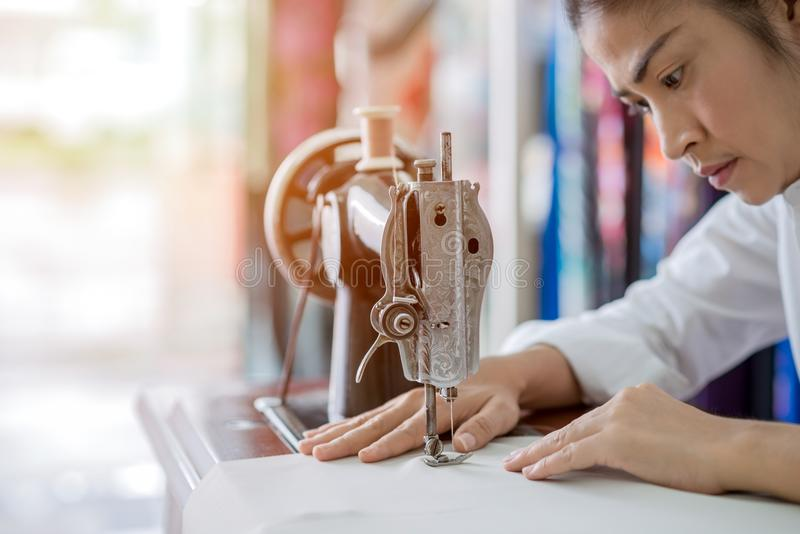 De vrouw naait thuis met naaimachine stock foto's