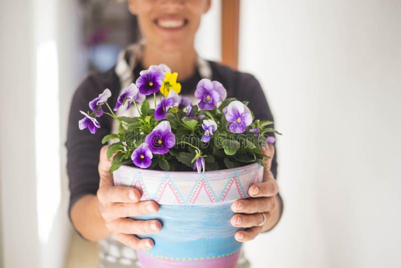 De vrouw neemt een vaas van violette bloemen stock foto's