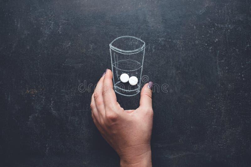 De vrouw neemt geneesmiddelen met glas van waterkrijt op bord wordt getrokken dat Sluit omhoog van vrouwenhand die in pil in getr stock fotografie