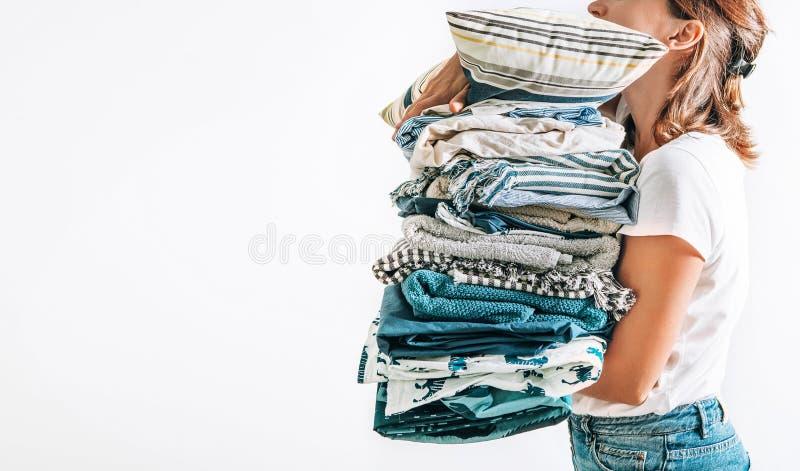 De vrouw neemt in handen grote stapel blauwe en beige dekens, handdoeken stock fotografie