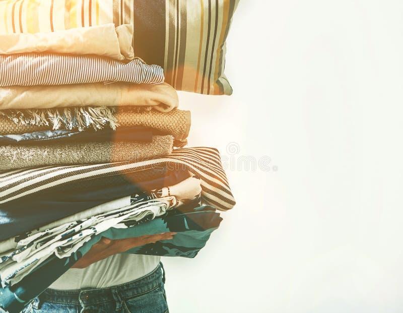 De vrouw neemt in handen de grote textiel van het stapelhuis voor het strijken stock afbeelding