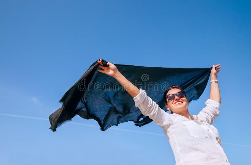De vrouw neemt in handen lichte sjaal die op de wind fladderen stock fotografie