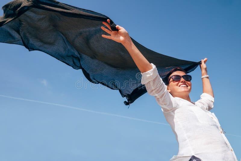 De vrouw neemt in handen lichte sjaal die op de wind fladderen royalty-vrije stock foto