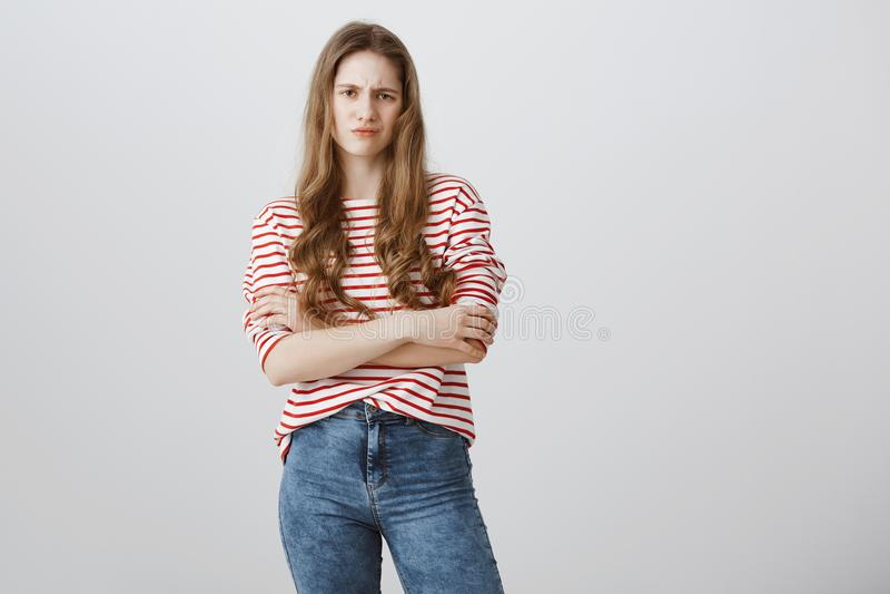 De vrouw is niet in stemming voor kinderachtige spelen Portret van mooie ernstige blonde tiener status met gekruiste handen stock afbeelding