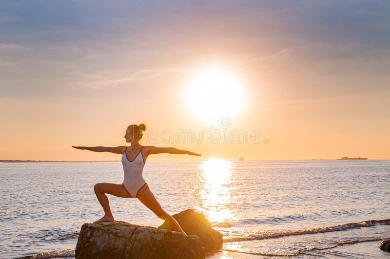 De vrouw oefent yoga bij zonsondergang op steen uit Silhouet van yogavrouw op het strand bij zonsondergang royalty-vrije stock afbeeldingen