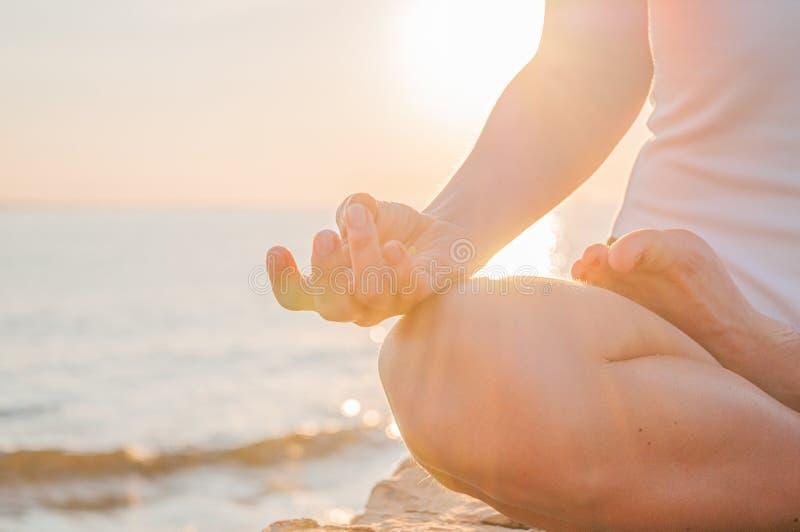 De vrouw oefent yogazitting in Lotus uit stelt bij zonsopgang Silhouet die van vrouw bij zonsondergang op het strand mediteren stock afbeelding