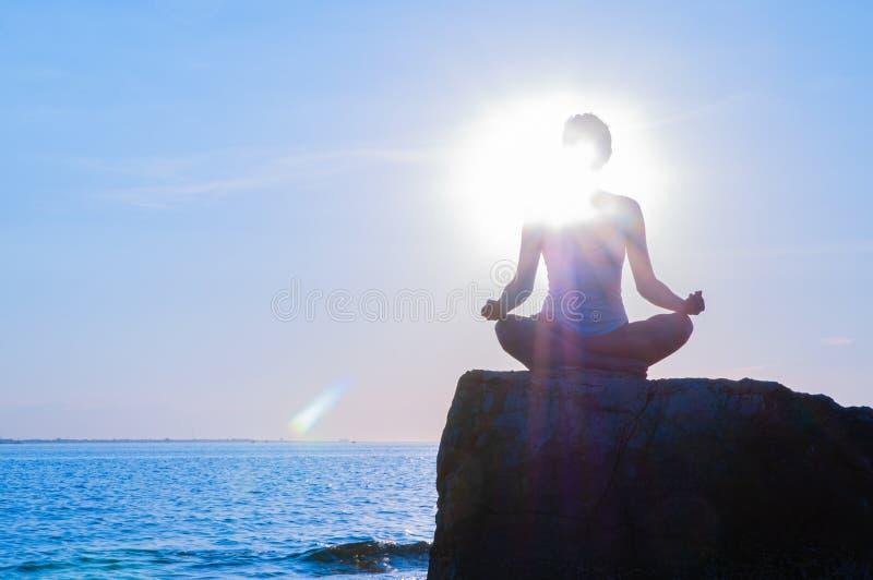 De vrouw oefent yogazitting op steen in Lotus uit stelt bij zonsondergang Silhouet die van vrouw op het strand mediteren stock afbeelding