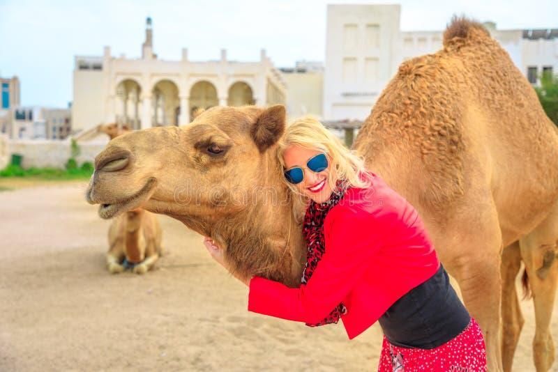 De vrouw omhelst kameel stock foto