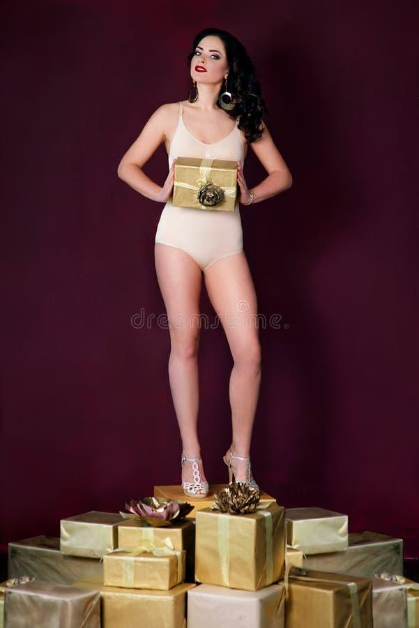 De vrouw in ondergoed die zich stelt dozen voor bevinden royalty-vrije stock afbeeldingen