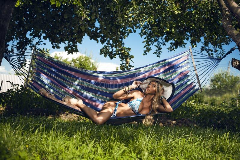De vrouw in ondergoed heeft een rust in een hangmat royalty-vrije stock afbeeldingen