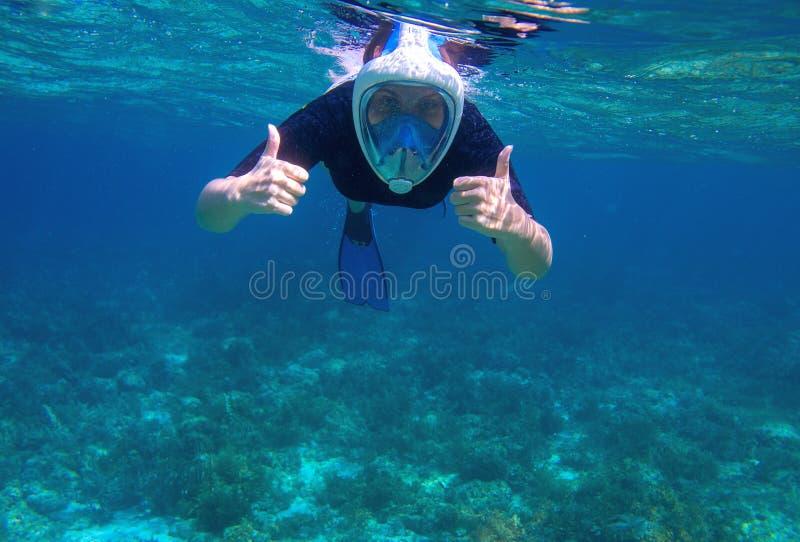 De vrouw onderwater toont duim Snorkel in koraalrif van tropische overzees Jong meisje in volledig-gezichts snorkelend masker stock foto's