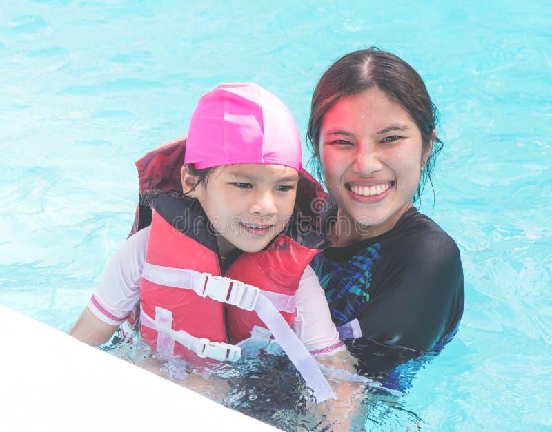 De vrouw onderwijst een klein meisje om te zwemmen royalty-vrije stock afbeelding