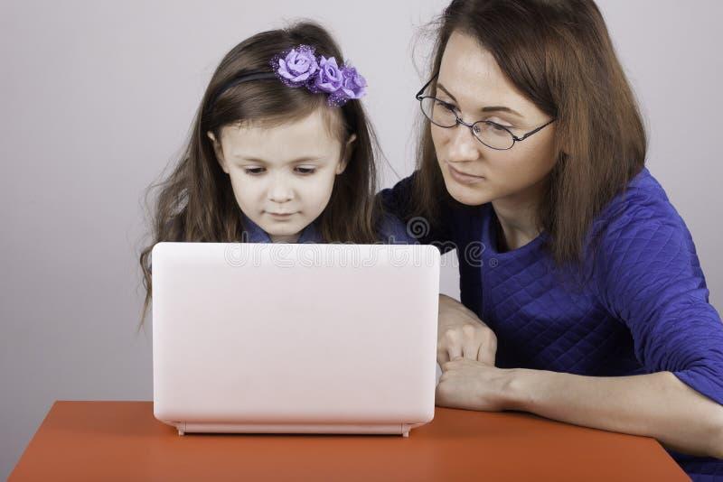 De vrouw onderwijst het kindwerk aangaande de computer stock afbeeldingen
