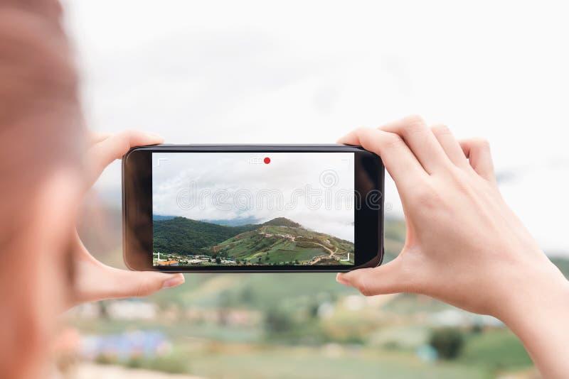 De vrouw onthoudt een video op haar telefoon De technologieconcepten maken het leven gemakkelijker waar u bent royalty-vrije stock fotografie