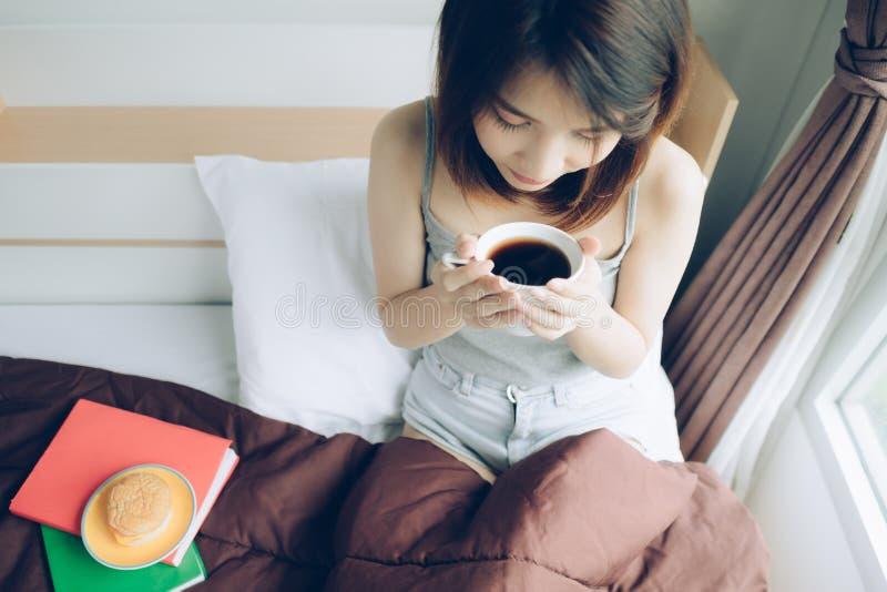 De vrouw ontspande op bed met kop van koffie in handen, hoogste mening ochtend, vrije tijd, mensenconcept - gelukkige jonge vrouw royalty-vrije stock fotografie