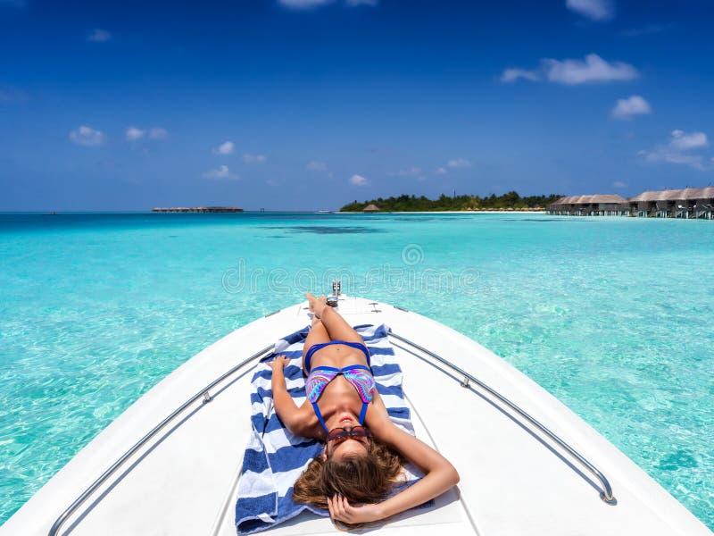 De vrouw ontspant op een jacht in de eilanden van de Maldiven royalty-vrije stock afbeelding