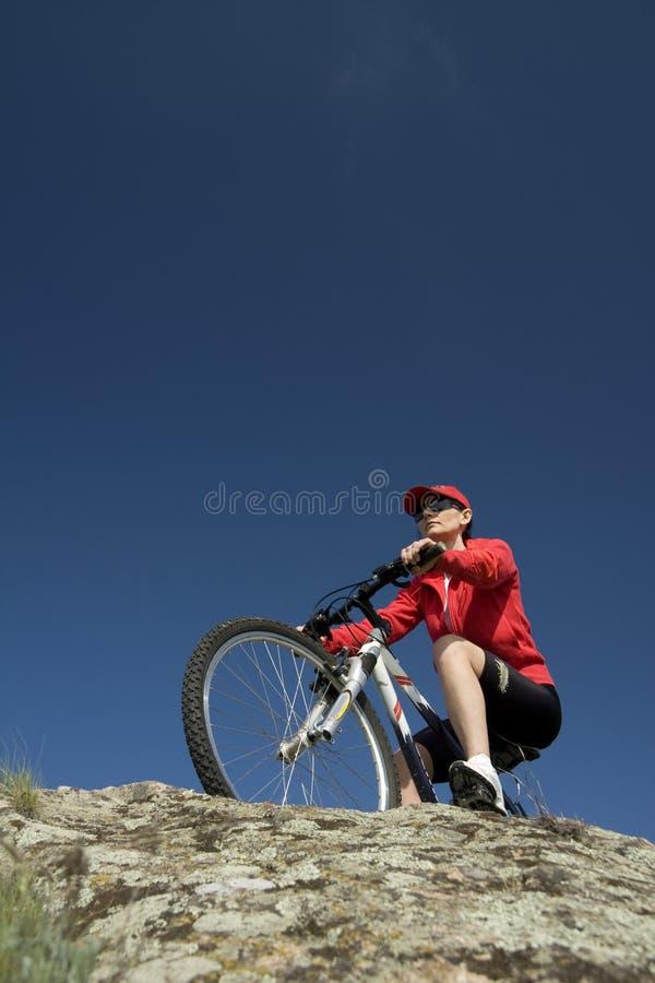 De vrouw op bergfiets stock afbeeldingen