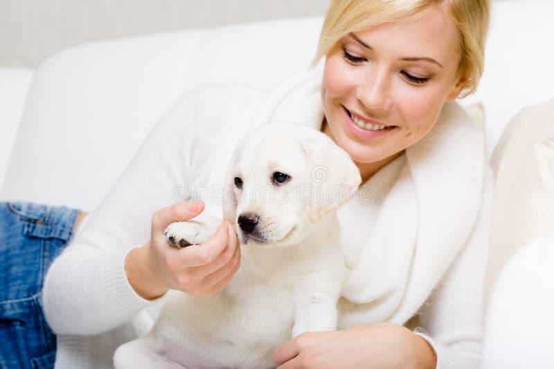 De vrouw is op de bank met wit puppy stock foto's